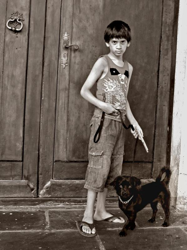 Black and White photo of a boy with a dog standing in front of a door